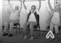 Older ladies exercising while sat down