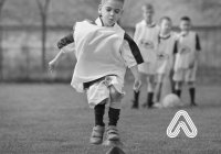 Young boy playing football Amaven