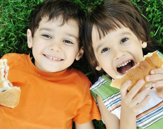 Two Children Lying on Grass & Eating Sandwiches