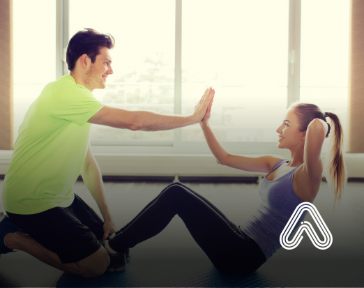 man and woman high fiving in gym