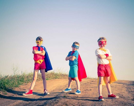 Three Children Posing in Superhero Capes and Masks