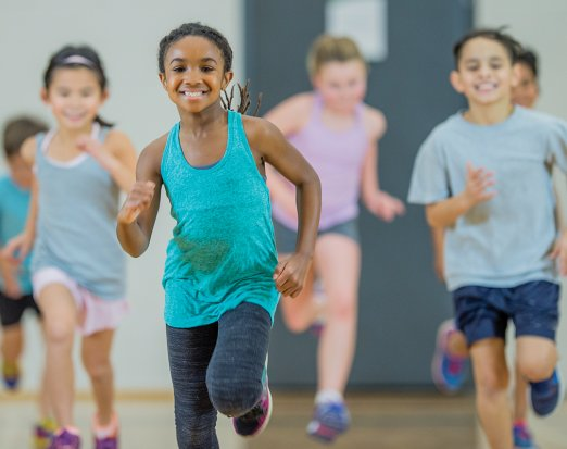 Young Children Smiling and Jogging in Gym Class