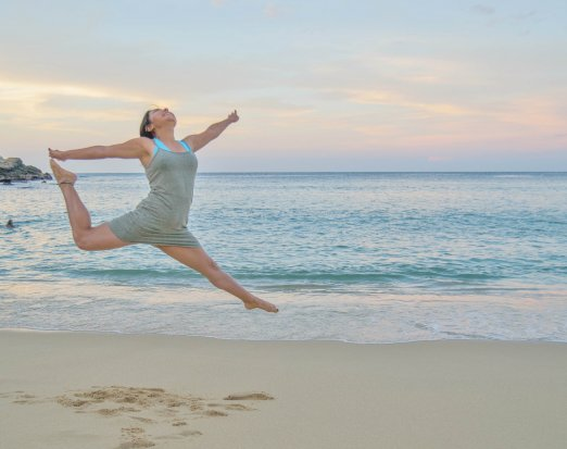 Athletic Woman in Grey Dress Leaping on Beach