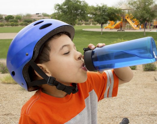 Young Boy in a Blue Bike Helmet Drinking from a Water Bottle