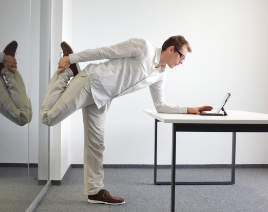 Man in white shirt stretching at desk