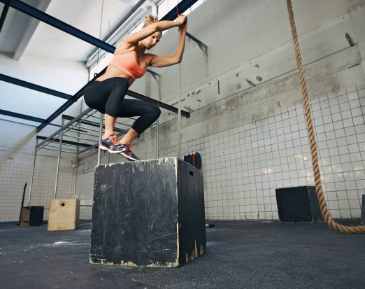 Woman jumping on box in gym