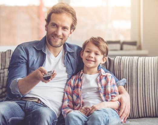 Man and child sat on sofa watching tv