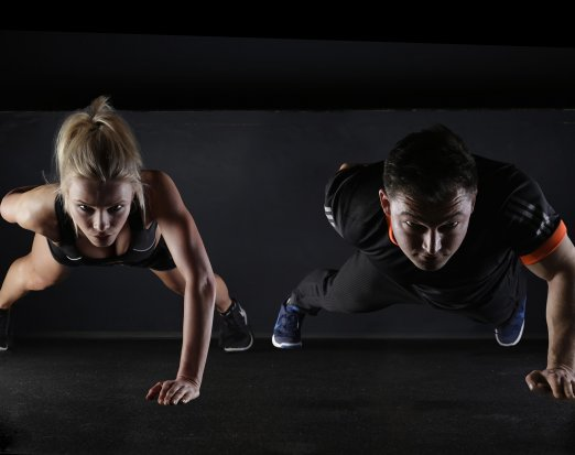 Two fitness models doing press ups