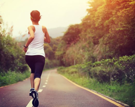 woman jogging down wooded road