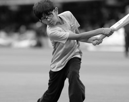 Young Boy in Glasses Swinging a Bat on a Cricket Field