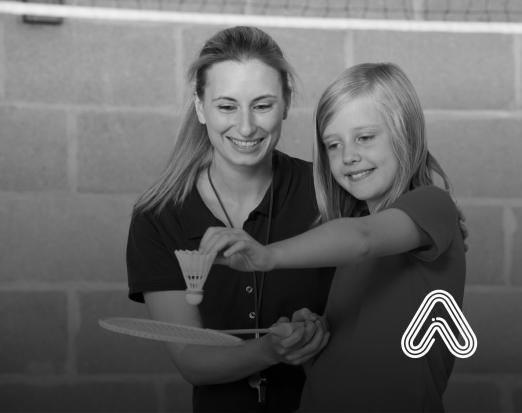 PE teacher helping girl to play badminton