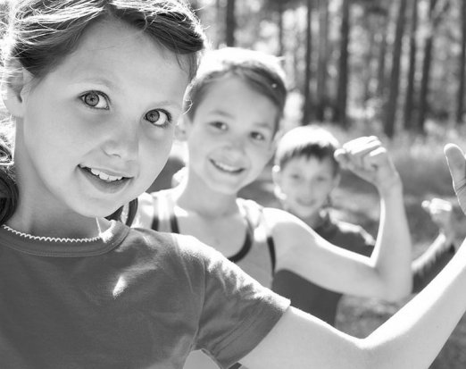 Three Children Flexing Their Biceps to Show Strength