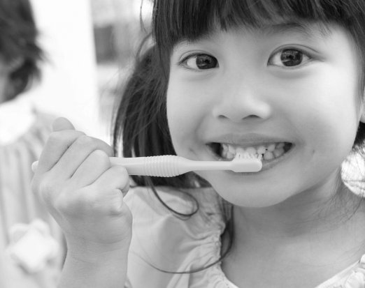 Young Girl Demonstrating Proper Toothbrushing Technique
