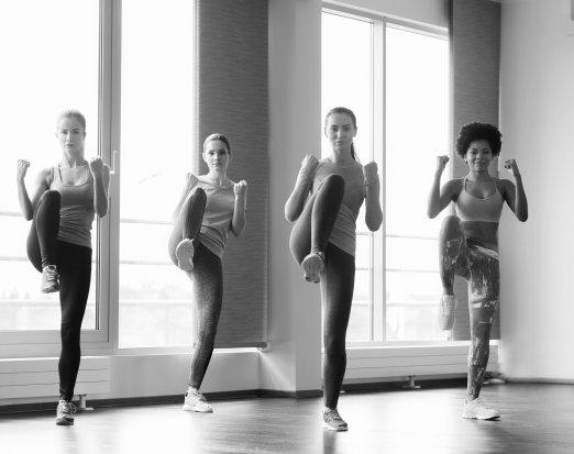 Four Women Doing Kick Exercises in Gym Clothing