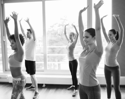 five women stretching their arms in a fitness class