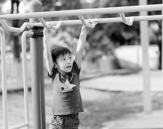 Boy doing monkeybars climbing frame