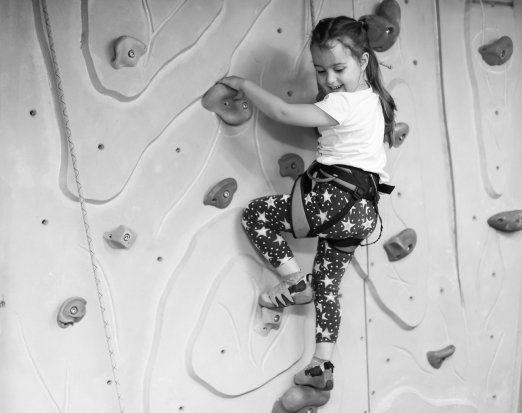 Young girl indoor rock climbing smiling