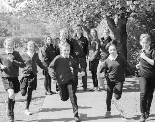 School Kids in School Uniform Running in Front of Their Teachers