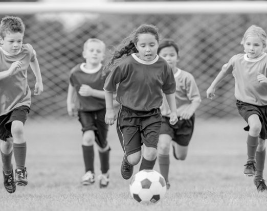 5 Children in Footie Kits Chasing a Football