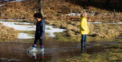 Two Children in Winter Clothes Splashing In a Stream