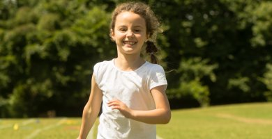 Young girl running and smiling outdoors