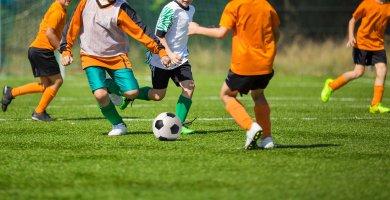 Five Boys in Orange Shirts Playing Football