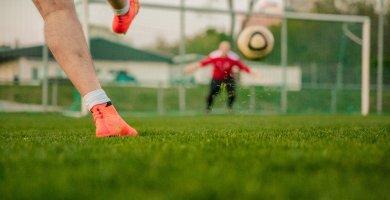 Boy Kicking Football at a Goalie