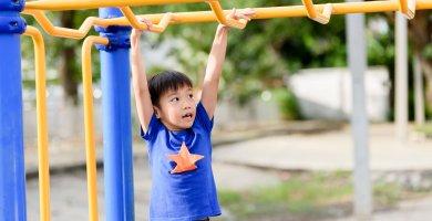 Boy doing monkeybars climbing frame