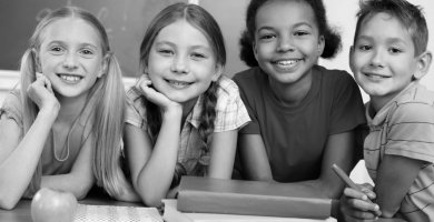 Four Smiling Children with Books and an Apple